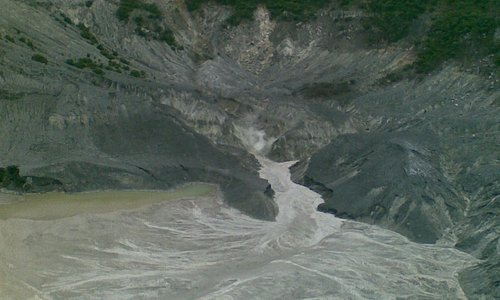 The crater of Tangkuban Parahu Mountain with sulphuric smoke out of its surface