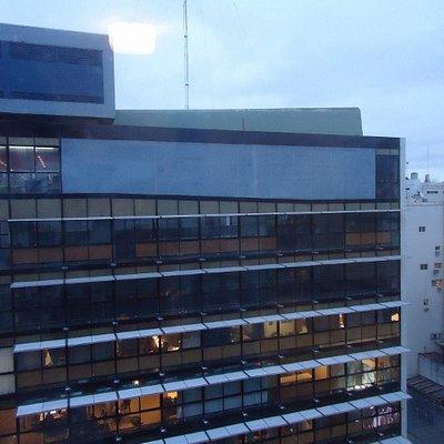 Frente,10 pisos,paneles de vidrio.