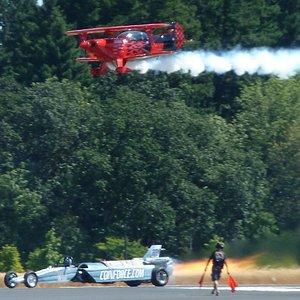 Jet car drag racing against biplane