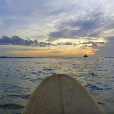 Sitting on the surfboard as today's surfing session comes to an end with the sunset.
