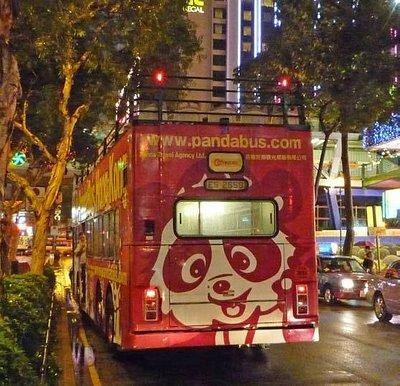 かわいらしいパンダ柄のバスが夜の香港の街を走る。頭上には看板。