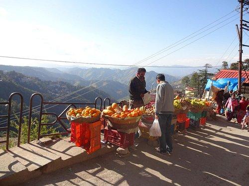 Fruit and veg stall Lakkar Bazaar and Himalayan backdrop