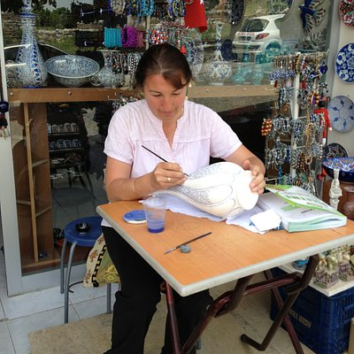 This is the owner of the shop sitting outside Hand Painting the Ceramics