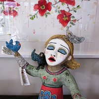 A whimsical sculpture with a cheerful print in the background