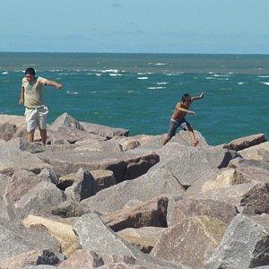 crianças correndo sob as pedras ao fim do caminho