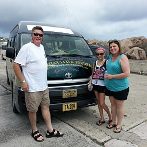 Guests taking a post in front of one of the choice Kittitian Taxi and Tour bus