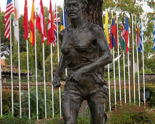 Statue in front of the museum with the flags of the winners of the Olympic Marathon in the backg