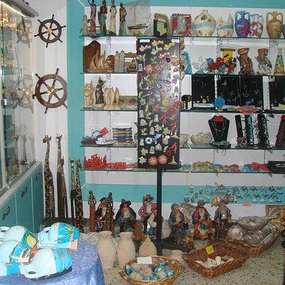 assortimento di souvenir locali..ceramica bigiotteria conchiglie abbigliamento ect