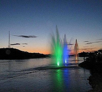 красочные фонтаны на реке