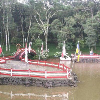 Lago com pedalinhos e bosque ao fundo.