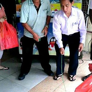 uncle Wong teaches tourists how to spin the old school gasing (Malay for top)