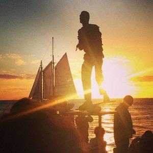 Performer and sail boat at sunset.