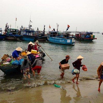 Boat full of food arriving at village