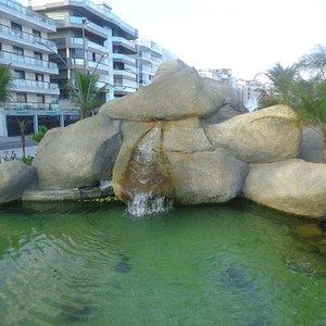 Águas descem pelas pedras.