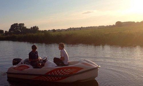 Ouders op terras, locale jeugd per boot