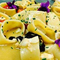 Mezzi Paccheri con gamberi e seppie su crema di ceci ai crostacei con fiori eduli e nero di sepp