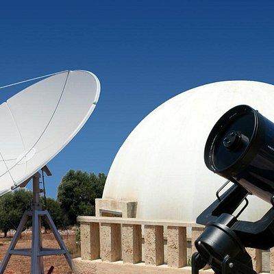Il radiotelescopio e uno dei telescopi ottici, sullo sfondo della cupola del planetario.