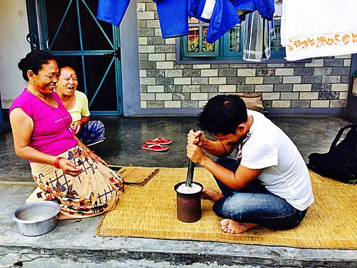 Beating rice to make Sel Roti