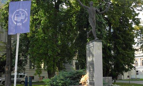 Скульптура марафонца и олимпийский огонь