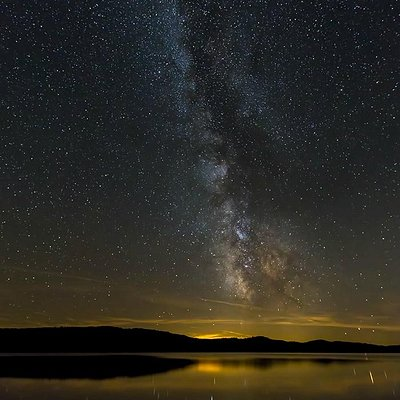The Milky Way shines high above the lake with the lights of Huntsville in the distance