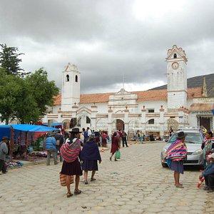 Puestos de artesanía al lado de la plaza, atrás la Parroquia de San Pedro de Montalban de Tarabu