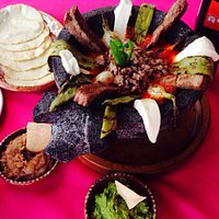 El molcajete. Hot stone bowl served with tender arrachera meat, panela cheese, nopal, onion and