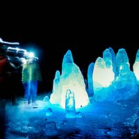 the insides of the cave are lit up and the ice is transparent and clear