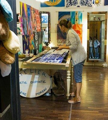 Helene painting a silk scarf in the shop