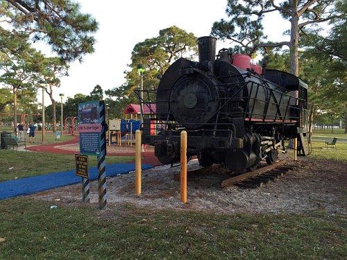 Antiga locomotiva com playground ao fundo.