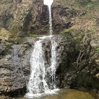 岩に開いた穴から滝が流れ落ちる