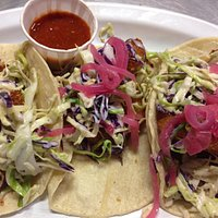 Grilled Shrimp tacos topped with cole slaw & pickled onion