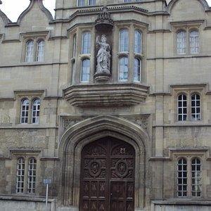 A grand doorway with a a lovely statue on Top with cycles of students attending classes. — in Ox