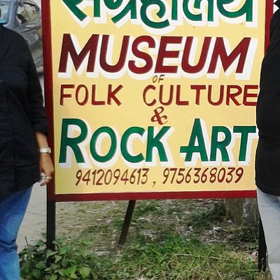 The Museum's Board on the roadside, with the buildings partly below the road level.