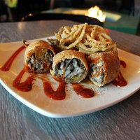 Cheese steak egg rolls stuffed with peppers, onions and mushrooms in a dish of sriracha ketchup!