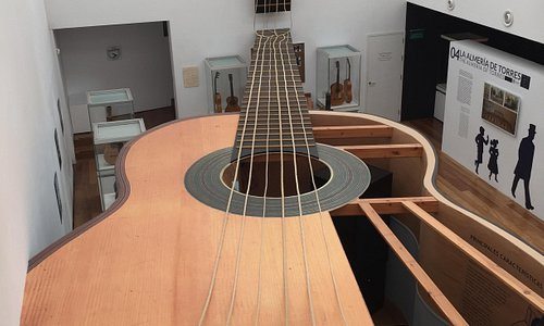 A giant guitar stands on the ground floor, the fret reaching to the floor above.