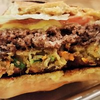 Beef patty on top, veggie burger below, in the Conflicted Burger.