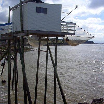 Vissershuis met grote visnetten.