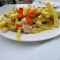Pork in sauce with fries and vegetables