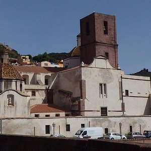 Bosa Cathedral with dark square bell tower; on the hill background lies the castle