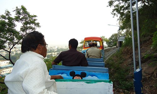 People riding toy train at the hill.