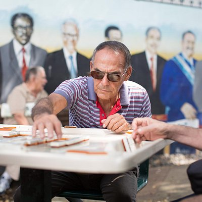 Awesome dude plays dominos in front of mural at Domino Park