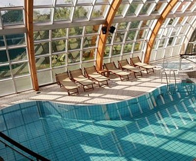 Interior - swimming pool with jacuzzi, rest area and a glimpse of the nudist garden.