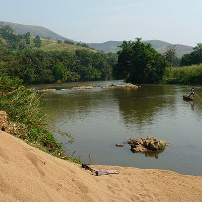 canoe poled by young man on Menchum river above falls