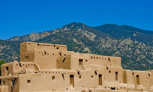 The bright baked walls of Taos Pueblo glow in the morning sunlight.