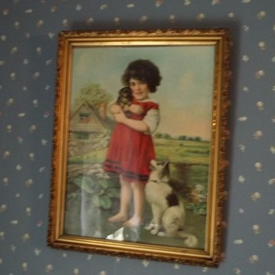 A very old picture of a child with her pets in the children's bedroom