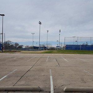 Parking area near some baseball diamonds