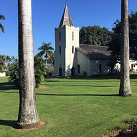 A nice lawn with palm trees. There is a graveyard behind the church as well.