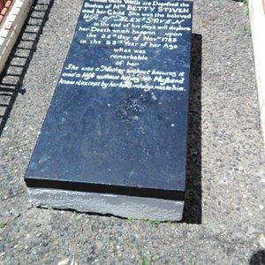 Grabstein mit Inschrift von kleinem Podest aus photografiert
