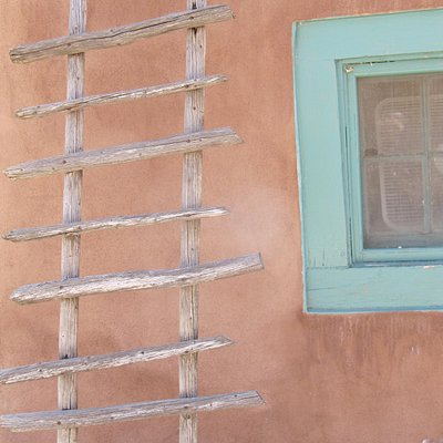 Lovely shot of stucco walls and turquoise window outside the kitchen at Mabel Dodge Luhan House