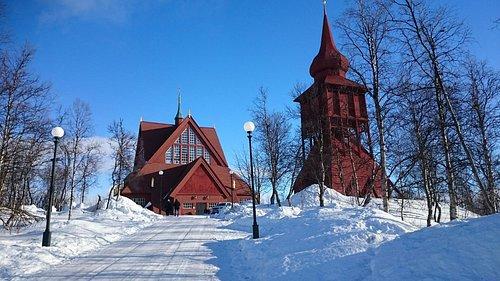 Kyrkan sedd utifrån i vinterskrud och solsken.